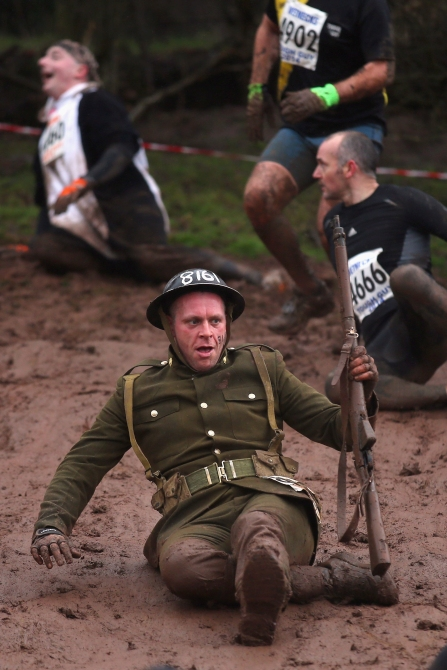 A competitor slides down a mud banking during the Tough Guy Challenge in Telford, England.