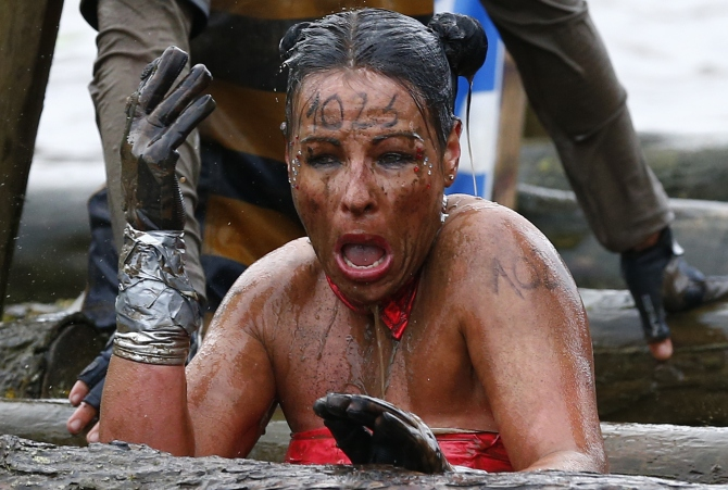 A competitor reacts as she emerges from the water during the Tough Guy event.