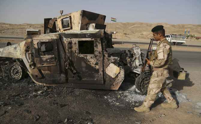 A Kurdish soldier walks past an Iraqi army vehicle destroyed by ISIS fighters
