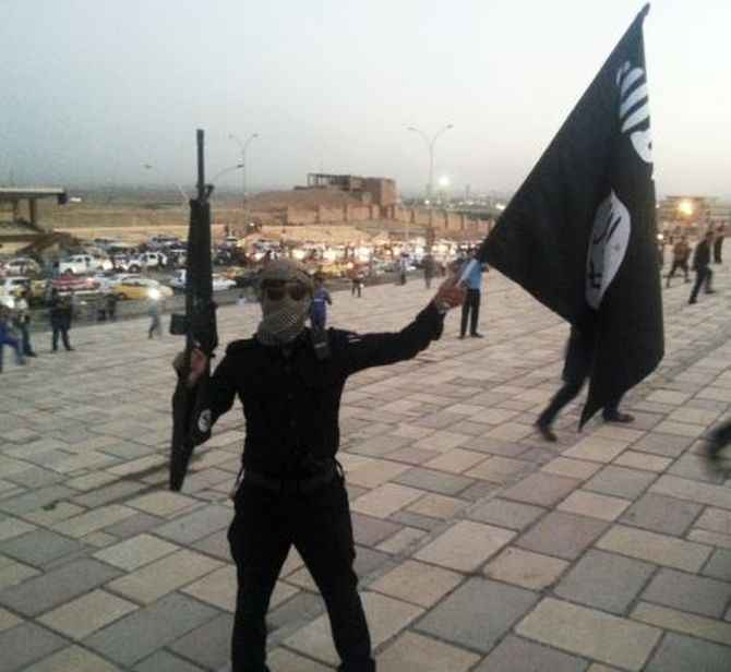An ISIS fighter holds an flag and a weapon on a street in Mosul, Iraq
