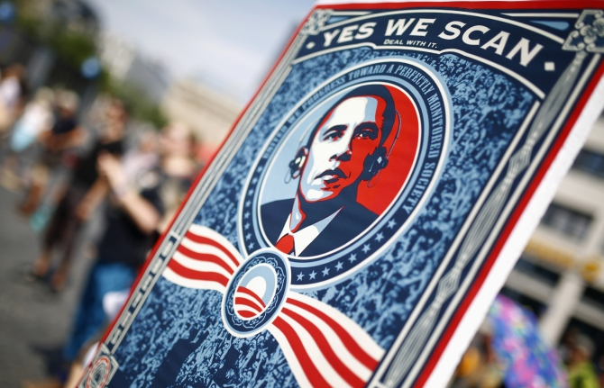 A protester holds a placard showing U S President Barack Obama with the phrase Yes we scan during a demonstration against the National Security Agency and in support of whistleblower Edward Sn