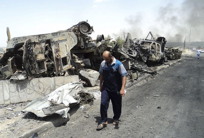 A man walks past cars, which have been reduced to debris owing to the terror activities of the Sunni rebels.