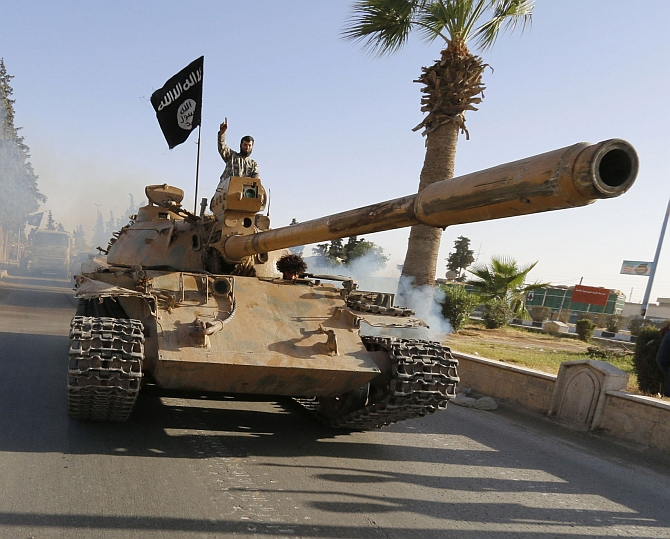 Militant Islamist fighters on a tank take part in a military parade along the streets of northern Raqqa province of Ir