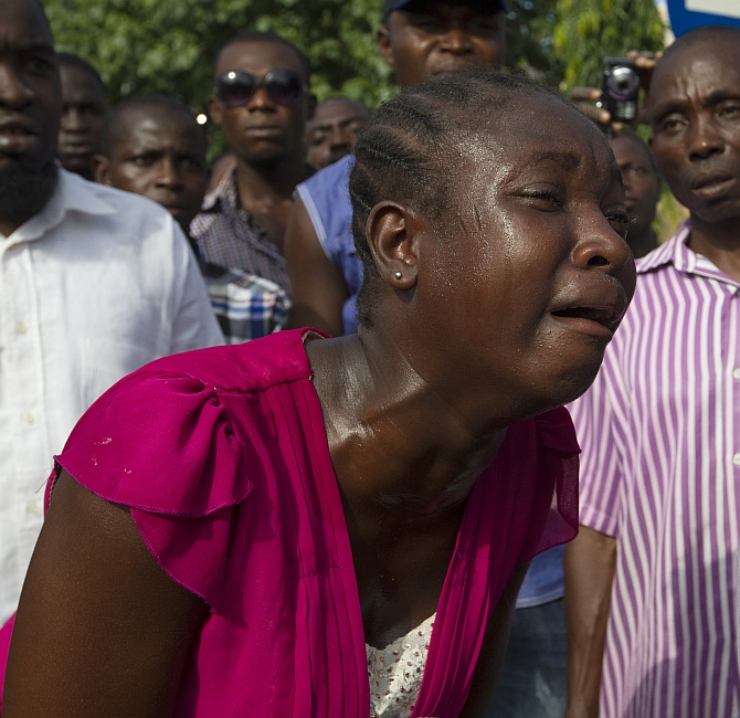A woman weeps at the scene of bomb blast carried out by Boko Haram at a crowded shopping district in Abuja, Nigeria