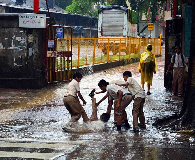 Children play in a puddle of water outside their school in Dadar, Mumbai