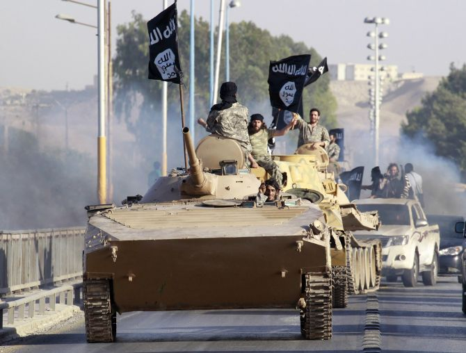 Militant Islamist fighters take part in a military parade along the streets of northern Raqqa province in Syria.