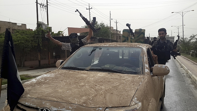 ISIS terrorists celebrate on vehicles seized from Iraqi security forces. Photograph: Reuters