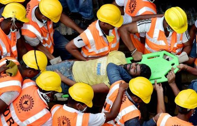 NDRF authorities rescue a man from the debris of the building in Chennai