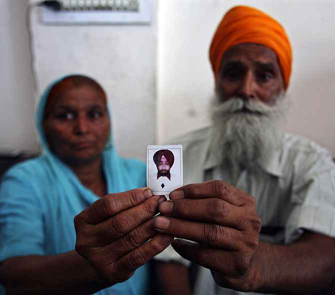 The parents of a construction worker stranded in Iraq show their son's photo, in Amritsar.
