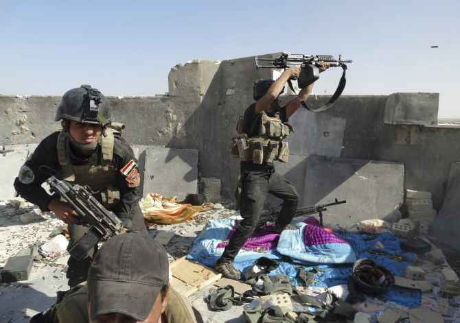 Iraqi security forces engage in a gun battle with ISIS fighters in Tikrit.