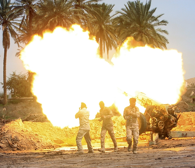 Iraqi security forces fire an artillery gun during clashes with the Islamic State in Iraq and Syria in Jurf al-Sakhar