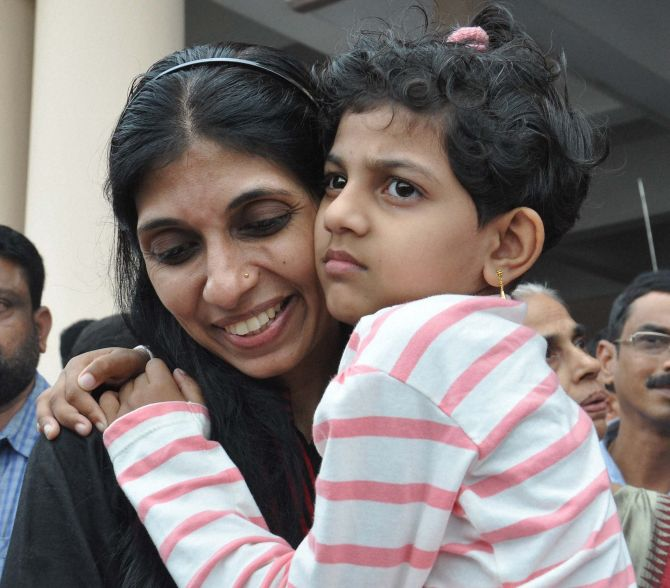 Maureen, one of then nurses who were stranded in the territory held by Islamic extremists in Iraq, holding her kid upon arrival at the airport in Kochi on Saturday