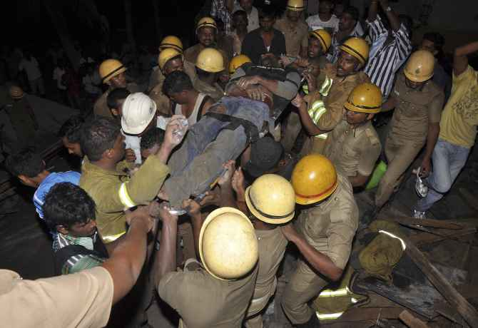 Rescue workers pull out an injured man from the rubble of an under-construction building that collapsed in Porur near Chennai
