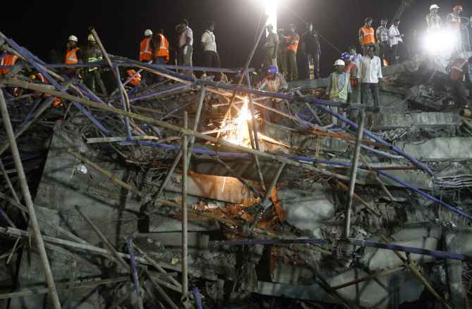 Rescue workers conduct a search operation for survivors at the site of the collapsed building near Chennai