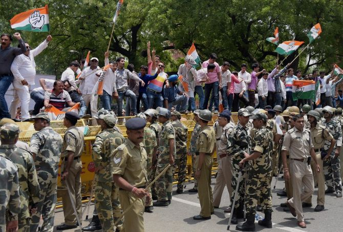 Congress workers shout slogans and wave party flags as they stand on a police barricade during a demonstration against price rise at Parliament Street