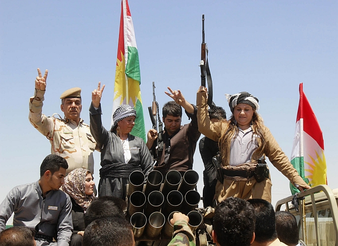 Members of the Kurdish Peshmerga celebrate in the city of Kirkuk