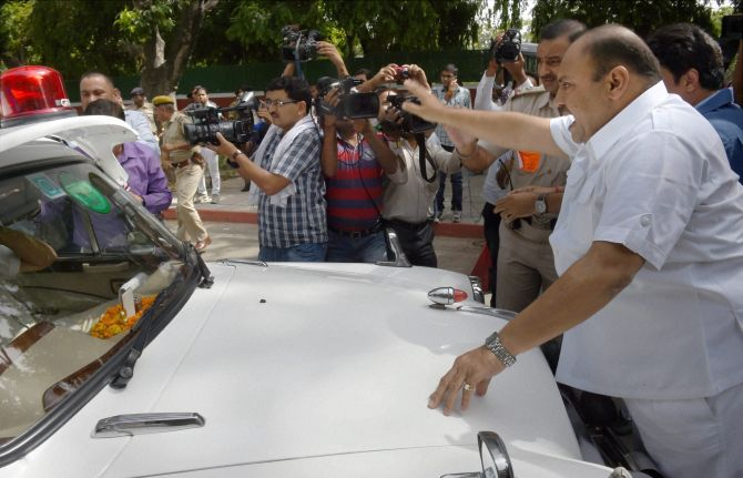 Mukesh Sharma stands in front of the car of Railway Minister DV Sadananda Gowda during the protest