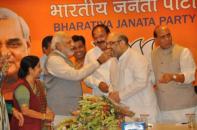 Prime Minister Narendra Modi offers sweets to new BJP president Amit Shah. Also seen are Sushma Swaraj, Venkaiah Naidu and Rajnath Singh