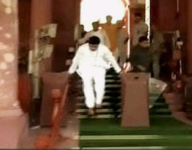 : An MP jumps at the gate as he walks out after a protest in the Lok Sabha over the Rail Budget.