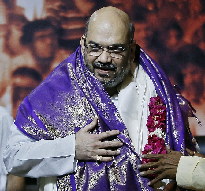 Amit Shah, the newly appointed president of the ruling BJP smiles during a news conference in New Delhi