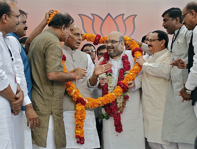 Shah receives a garland by BJP members in New Delhi