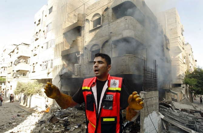 A member of the civil defence reacts after what police said was an Israeli air strike on a house, in Gaza City.