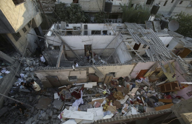 Palestinians inspect a house, which police said was damaged in an Israeli air strike on a neighbouring house, in Khan Younis in the southern Gaza Strip.