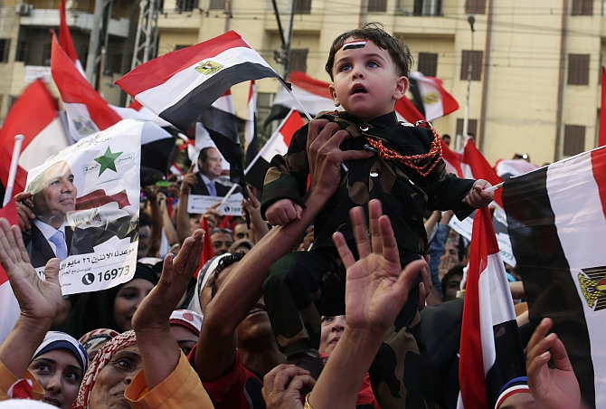 A child wearing military outfit is held up as Egyptians celebrate after the swearing-in ceremony of President elect Abdel Fattah al-Sissi, in front of the Presidential Palace in Cairo