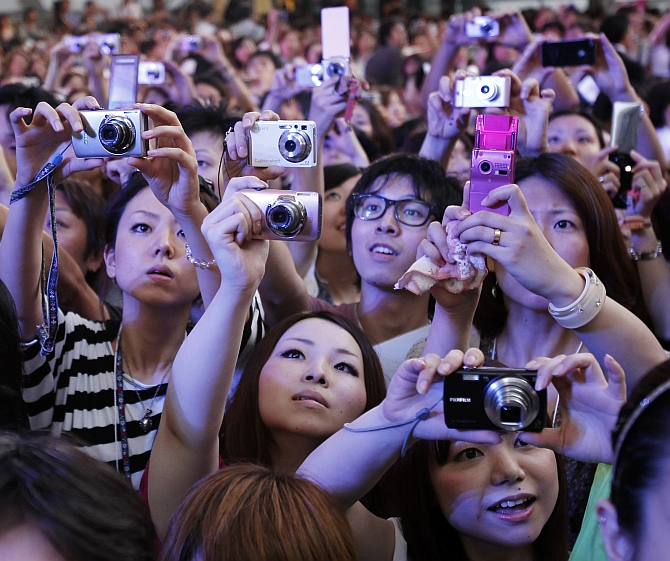 Fans take photos of celebrities arriving at a film premiere in Tokyo