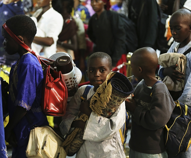 Refugees fleeing escalating violence in the Central African Republic, wait in line at the Nnamdi Azikiwe International Airport in Abuja