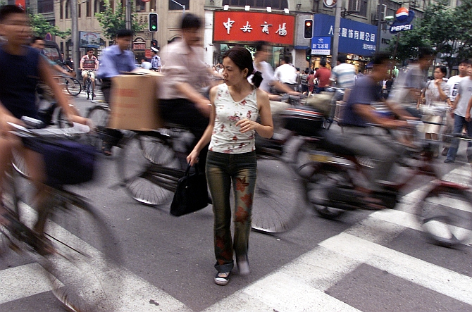 A Chinese woman struggles to cross a busy intersection in Shanghai