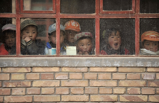 Children look out from a window of their classroom at a rural primary school in Min county, Gansu province, China