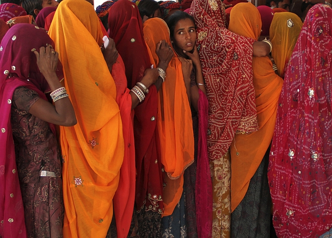 Women line up in a queue outside a polling booth to cast their vote