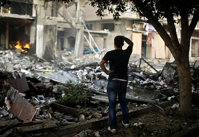 A Palestinian man looks at a house which police said was hit in an Israeli air strike, in Gaza City July 11