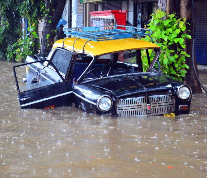 A taxi submerges as rains flood roads in Mumbai