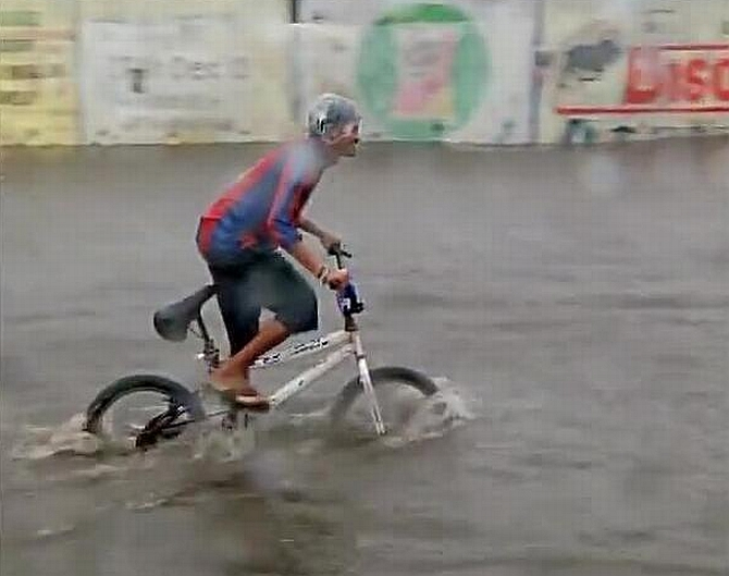 A man cycle through a flooded road in Mumbai