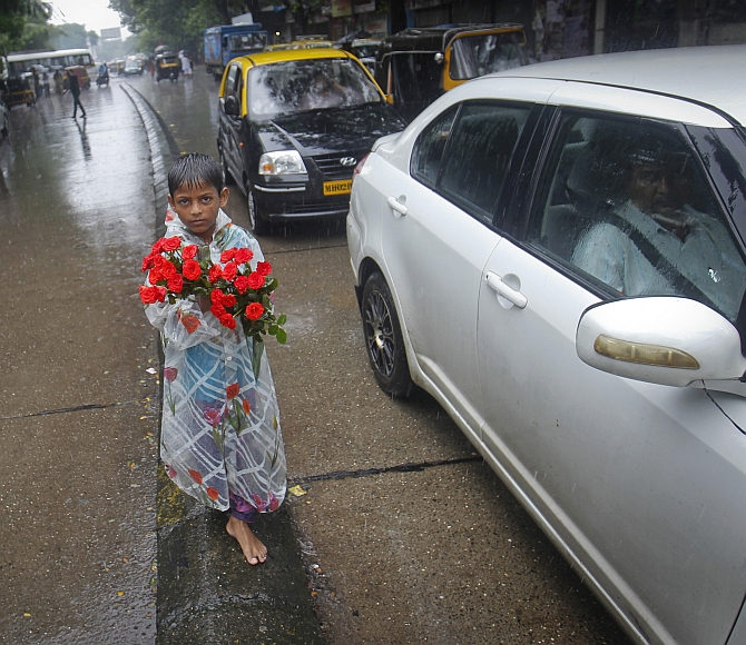 A boy sells roses while standing on a road divider during monsoon rains in Mumbai