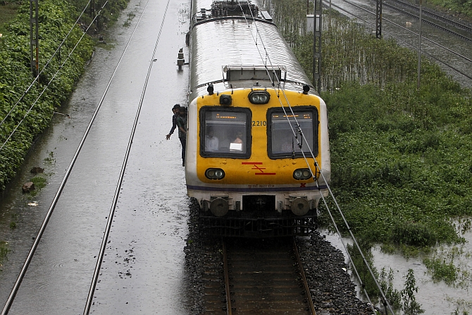 A suburban train passes over waterlogged railway tracks during heavy monsoon rains in Mumbai