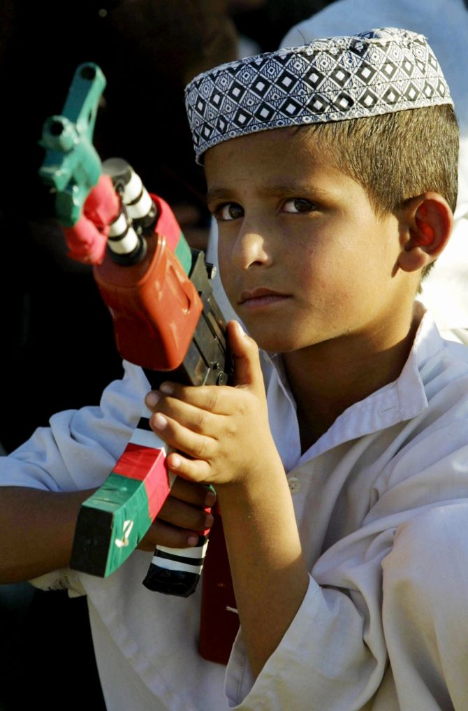 A little boy holds a gun in his hand in Pakistan.
