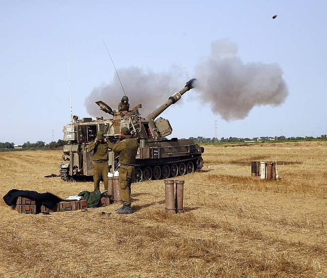 An Israeli mobile artillery unit fires towards Gaza from outside the central Gaza Strip July 12