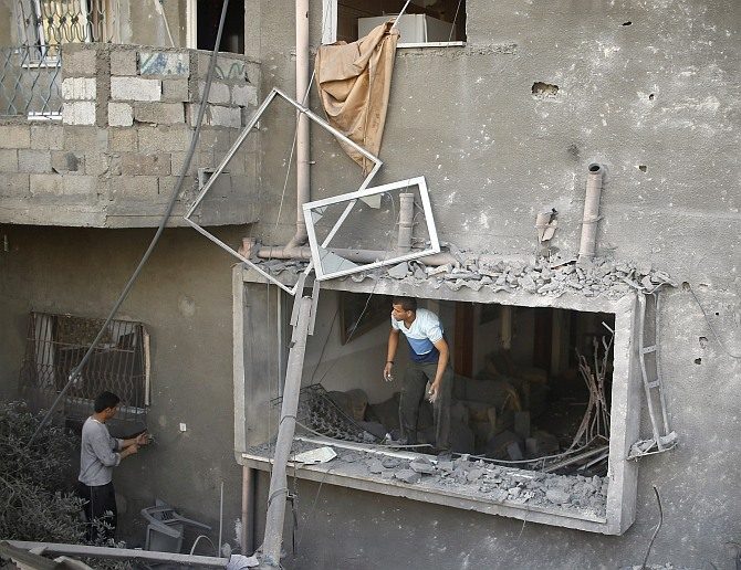 A Palestinian surveys a house which police said was damaged in an Israeli air strike on a neighboruing house in the northern Gaza Strip July 12