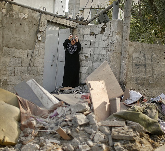 A Palestinian woman reacts after what police said was an Israeli air strike that destroyed a neighbouring house in the northern Gaza Strip July 12