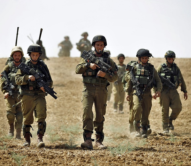 Israeli soldiers from the Nahal Infantry Brigade walk across a field near central Gaza Strip July 12