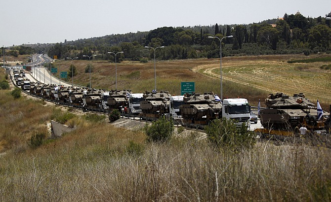 A convoy of Israeli lorries carrying army tanks can be seen on a road leading to southern Israel, at Latrun, near Jerusalem July 12