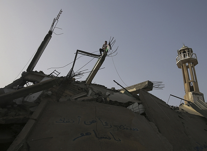 A youth puts up a Palestinian flag over the rubble of a mosque, which police said was destroyed in an Israeli air strike, in Nuseirat in the central Gaza Strip