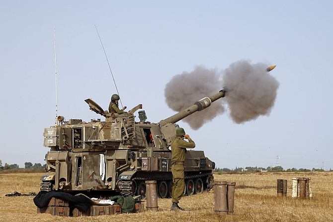 An Israeli mobile artillery unit fires towards Gaza from outside the central Gaza Strip