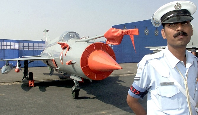 An Indian Air Force officer stands in front of a MiG-21 fighter