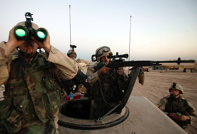 US army sniper takes aim at a suspected enemy observer looking in at Camp Eagle from a neighborhood outside of Sadr City, Baghdad