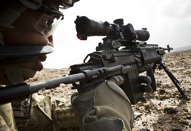 A US army sniper looks down the scope of his rifle during a mission near Command Outpost Pa'in Kalay in Maiwand District, Kandahar Province