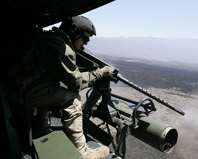 A US marine fires a machine gun at targets, from a Huey attack helicopter during live fire training for the multi-national military exercise RIMPAC at Pohakuloa Training Area on the island of Hawaii
